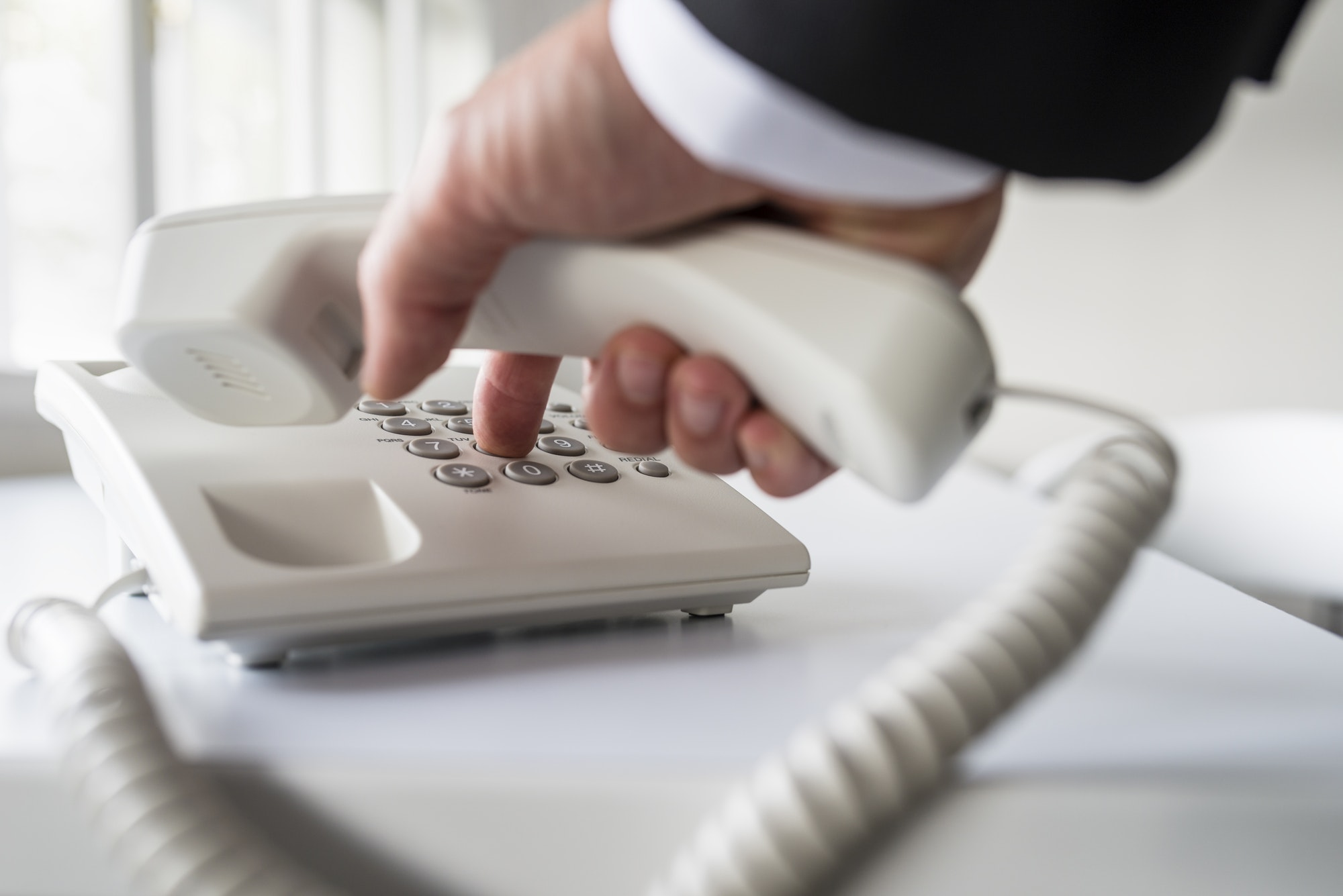 Businessman dialing a telephone number